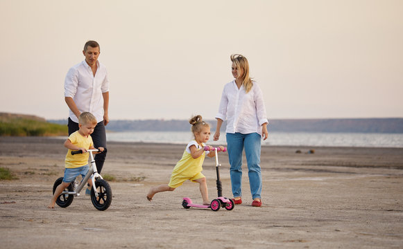 Mother and father with kids riding scooter and bike in summer. Family runs on the beach at sunset. Daughter and son learns to ride