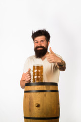 Wooden barrel and glass of beer. Oktoberfest. Bearded man with glass of beer shows thumb up....