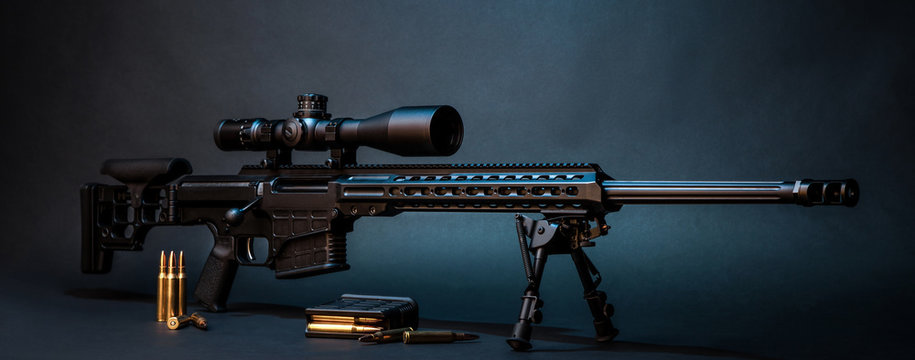 Modern powerful sniper rifle with a telescopic sight mounted on a bipod. Ammo and an additional magazine next to the rifle.