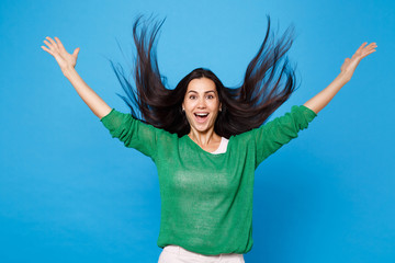Cheerful young woman in green casual clothes with fluttering hair fooling around, having fun jumping, rising hands isolated on blue background in studio. People lifestyle concept. Mock up copy space. Wall mural