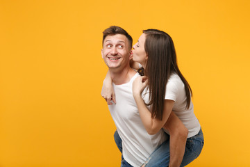 Pretty young couple guy girl in white t-shirts posing isolated on yellow orange wall background. People lifestyle concept. Mock up copy space. Giving piggyback ride to joyful sitting on back, kissing.