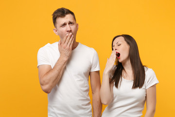 Young couple two friends guy girl in white empty blank design t-shirts posing isolated on yellow orange background. People lifestyle concept. Mock up copy space. Yawning, covering mouth with hands.