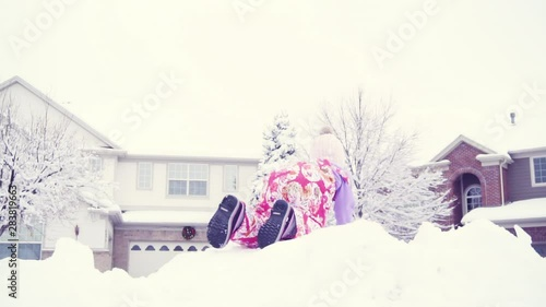 Wall mural Slow motion. Little girl in pink hat playing in snow.