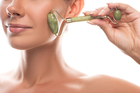 cropped view of naked young woman using facial jade roller and smiling isolated on white