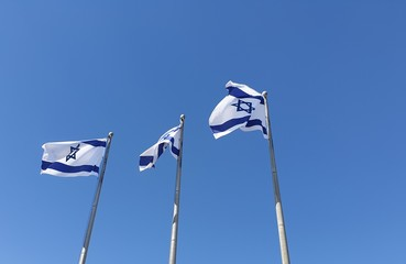 JERUSALEM, ISRAEL. August 13, 2019. A row of flags of Israel in front of the Israeli parliament Knesset. Israeli flags against the sky. Israel Independence Day concept.