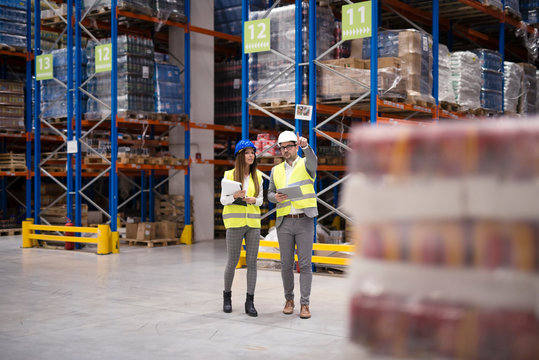 Warehouse managers walking through large warehouse distribution center discussing about increasing productivity.