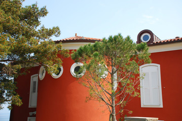 A modern building with a circular wall surrounded by trees outside the historic Slovenian coastal town of Piran