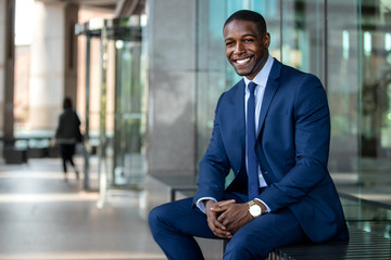 Handsome and stylish modern african american business man entrepreneur executive, sitting outside of office with cheerful smile Fototapete