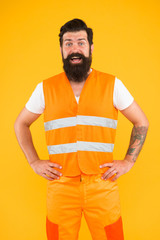 Safety apparel for construction industry. Bearded brutal hipster safety engineer. High visibility reflective safety vest. Man worker protective uniform orange background. Safety equipment concept