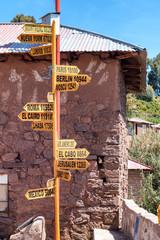 Distance signs found in a city square in Amantani, Peru on Lake Titicaca