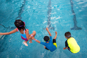 Happy children jumping into swimming pool