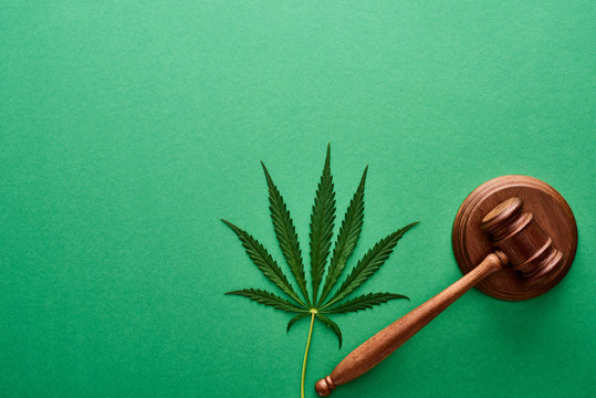top view of green cannabis leaf with wooden gavel on green background
