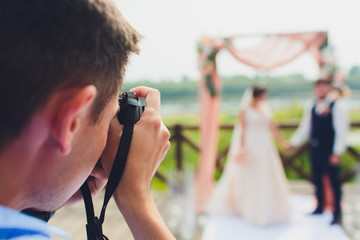 wedding photographer takes pictures of bride and groom in city. wedding couple on photo shoot. photographer in action.