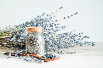 Glass bottle and wooden spoon with dried lavender flowers and bouquet with lavender on white wooden...