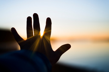 A hand is reaching for the sun with sun rays bursting thru