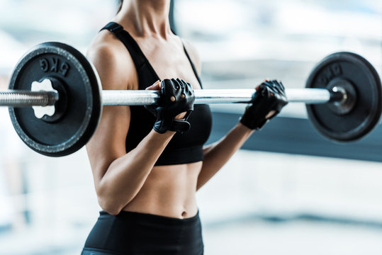 cropped view of young woman in sportswear exercising with barbell in gym