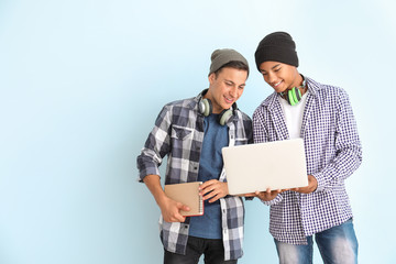 Portrait of young students with laptop on color background Wall mural