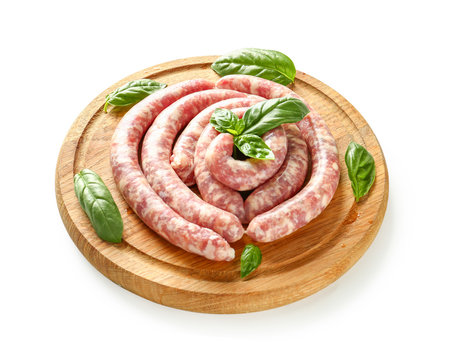 Wooden board with fresh raw sausages on white background