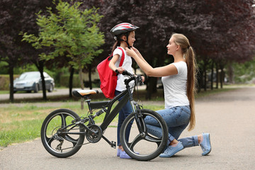 Mother helping her daughter to put on bicycle helmet outdoors Wall mural