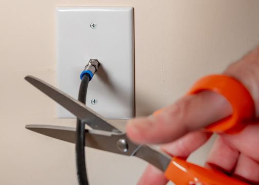 Cancelling cable TV service by cutting the coax cable connection. Close-up of male  hand using scissors to disconnect  television subscription.