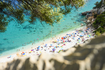 Wall Mural - (Selective focus) View from above, stunning view of a beautiful beach full of beach umbrellas and people sunbathing and swimming on a turquoise water. Cala Gonone, Sardinia, Italy.