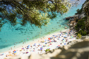 Fototapete - (Selective focus) View from above, stunning view of a beautiful beach full of beach umbrellas and people sunbathing and swimming on a turquoise water. Cala Gonone, Sardinia, Italy.