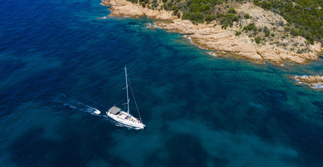 Fototapete - View from above, stunning aerial view of a sailboat sailing on a beautiful turquoise sea that bathes the green and rocky coasts of Sardinia. Emerald Coast (Costa Smeralda) Italy