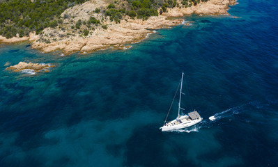 Wall Mural - View from above, stunning aerial view of a sailboat sailing on a beautiful turquoise sea that bathes the green and rocky coasts of Sardinia. Emerald Coast (Costa Smeralda) Italy