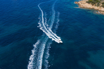 Wall Mural - View from above, stunning aerial view of a small boat sailing on a beautiful turquoise sea that bathes the green and rocky coasts of Sardinia. Emerald Coast (Costa Smeralda) Italy