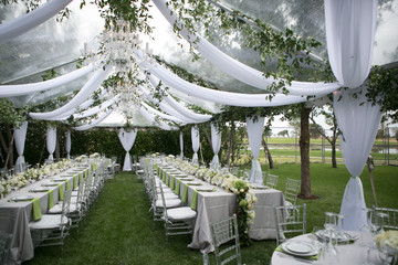 Outdoor summer wedding tent decorated with hanging fabric, greenery, and crystal chandeliers, wedding reception tables, green accent color