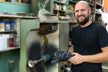 A male shoemaker posing next the grinder, holding a pair of sandals in his workshop.