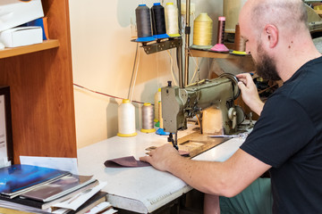 A male shoemaker sewing leather with an old sewing machine.