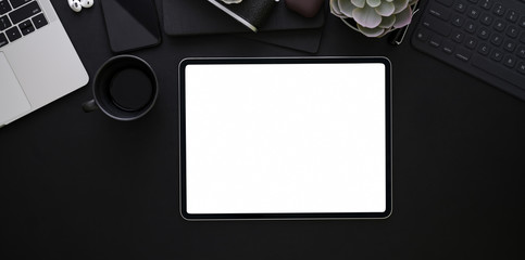 Blank screen tablet on black leather background in dark stylish workplace