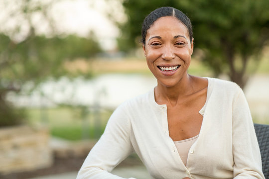 Mature confident African American woman smiling outside.