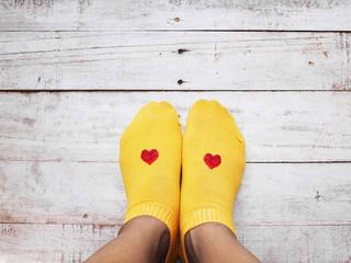 Selfie feet wearing yellow socks with red heart shape on wood background.