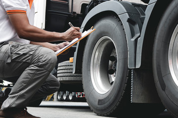 Truck driver holding clipboard daily checking safety checklist a truck wheels.