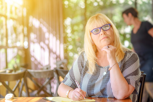 Portrait of beautiful plus size body positive woman working and making notes to her diary on sunny cafe. Elegant middle aged lady posing with modern glasses.Mature woman writer sitting writing notes.