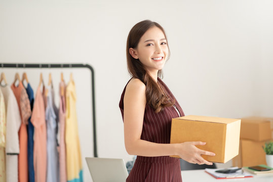 woman fashion designer standing and holding cardboard box.