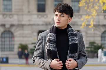 Portrait of a handsome Chinese young man in casual suit looking away with Shanghai bund background, winter fashion, cool young man lifestyle.