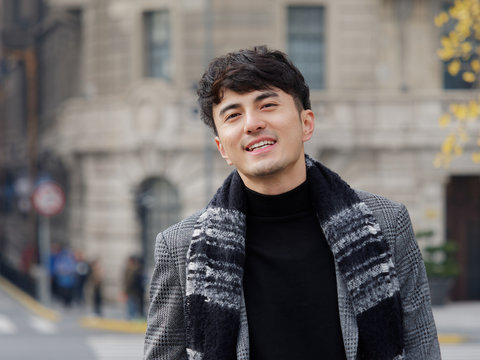 Portrait of a handsome Chinese young man in casual suit smiling and looking at camera confidently with Shanghai bund background, winter fashion, cool young man lifestyle.