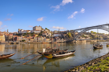Porto Portugal city skyline at Porto Ribeira and Douro River with Rabelo wine boat and Dom Luis I Bridge
