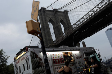People buy ice cream at an ice cream truck under the Brooklyn bridge in New York