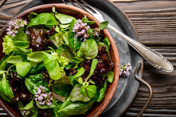 Top view at clay dish with green and violet lettuce, lamb's lettuce salad with oregano flowers on vintage metal tray. Fork aside