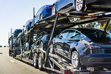 July 4, 2019 Redwood City / CA / USA - Car transporter carries Tesla Model 3 new vehicles along the highway in San Francisco bay area, back view of the trailer;