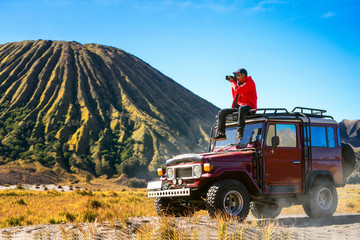 Wall Mural - Traveller sit and take a photo on a vintage off road car with Bromo mountain background