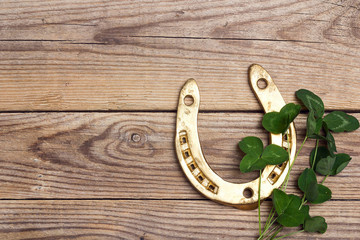 St.Patrick's Day. Golden horseshoes with clover leafs on wooden background.