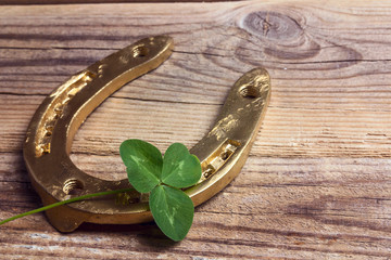 Golden horseshoes with clover leafs on vintage wooden background.