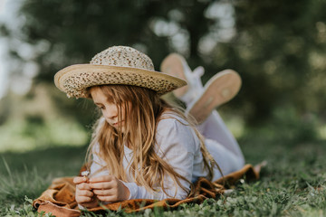 Young girl with hat lying in grass