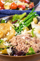 A traditional French 'Nicoise Salad' with a blue napkin on a bamboo placemat