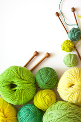 Knitting, needlework and hobbies. Green and yellow balls of yarn for hand knitting and wooden needles on a white background. Empty space for text. Flat lay, close up, macro